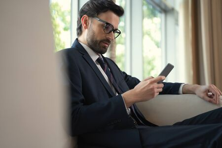 Smart male executive looking on screen of his smartphone