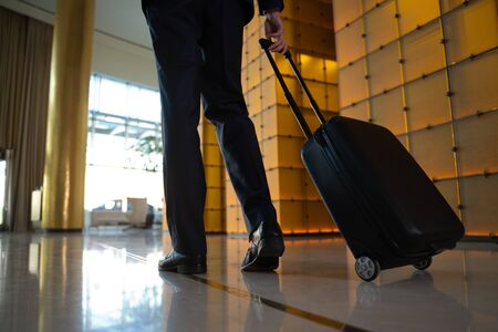 Male traveller with luggage arriving to business hotel
