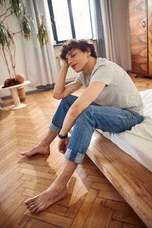 Attractive young man sitting on bed at home Banque d'images