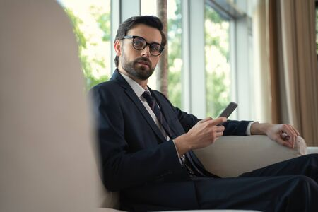 Pleasant young businessman with a cell phone thoughtfully looking aside