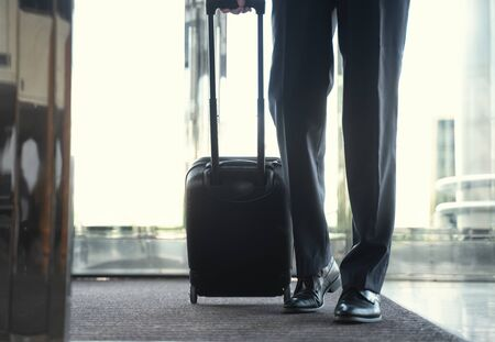 Cropped shot of a businessman entering hotel with luggage