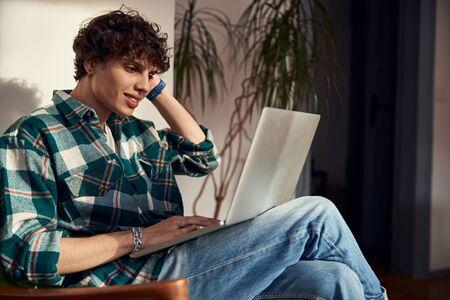 Joyful young man using modern laptop at home Banque d'images