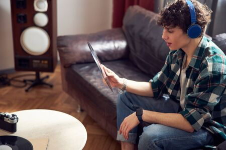 Handsome young man listening to old records at home