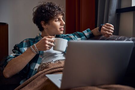 Handsome guy holding cup of coffee and checking time