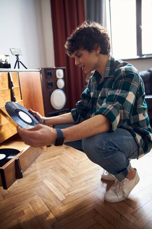 Handsome young man in shirt holding vinyl record