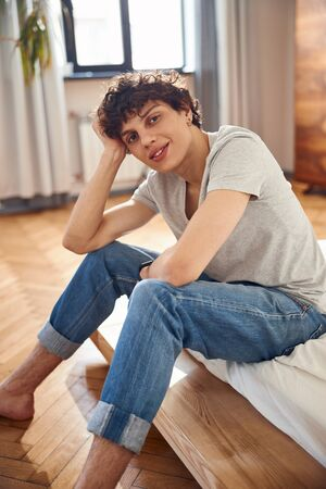 Joyful young man sitting on bed at home Banque d'images
