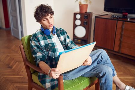Handsome young man looking at vinyl record