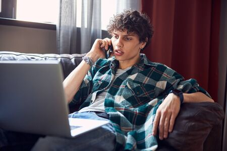 Attractive young man talking on mobile phone at home