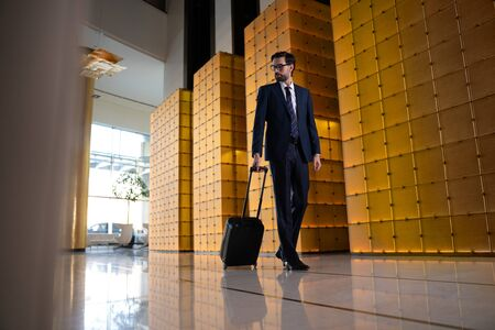 Serious young man arriving in hotel on business