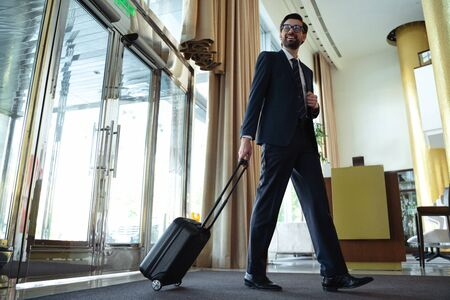 Smiling bearded traveller in formal attire reaching reception area with his luggage
