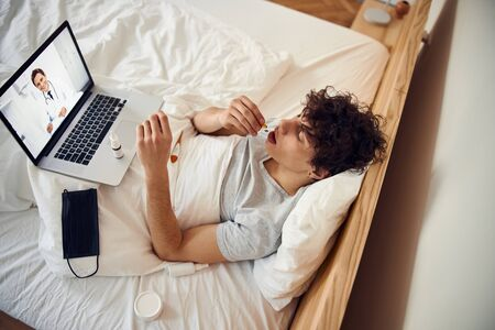 Sick guy taking pill while having online consultation with doctor Banque d'images