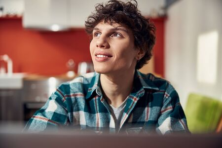 Attractive curly-haired guy is expressing positive emotions