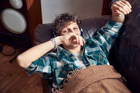 Curly-haired guy resting on couch and listening to music