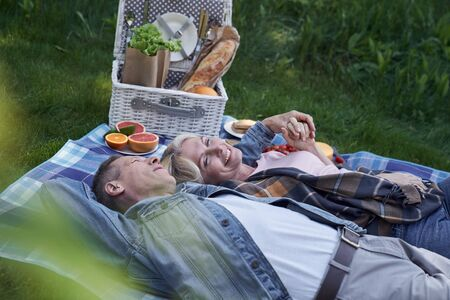 Happy mature couple is lying on grass ang embracing after eating healthy meals in green wood