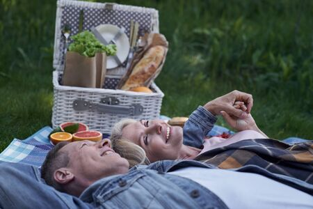 Jolly mature couple is lying on grass and embracing while having meals among green nature Banque d'images