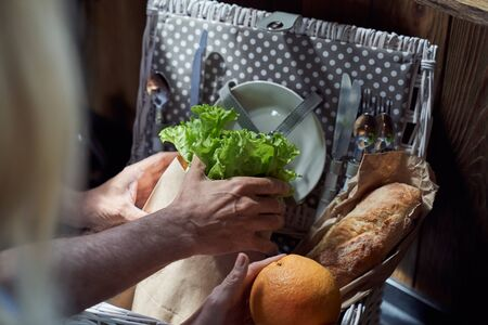 Cropped head close up of male and female hands packing bread with fruit and vegetables in kitchen before going on picnic