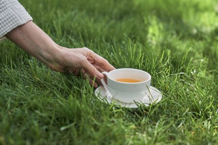 Close up of woman hand taking white porcelain mug of hot drink standing on grass