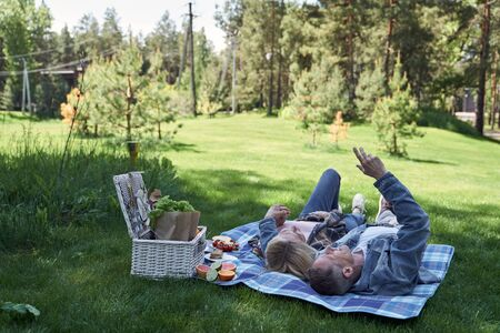 Loving man is embracing wife while they are lying on spread near basket with meals in countryside Banque d'images