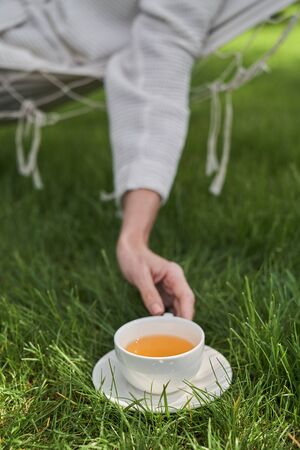 Close up of female hand holding cup of hot drink while she is lying in hammock in open air