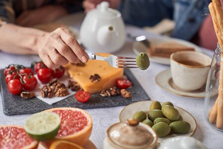 Close up top view cropped head of female hand holding fork with olive above table with cups of tea and fruit with vegetables