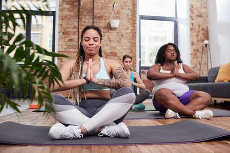 Restful women doing yoga exercises in home environment 版權商用圖片