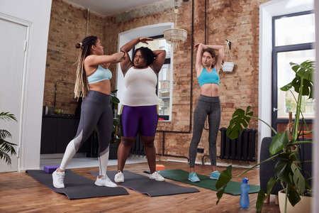Young enthusiastic women doing fitness with trainer