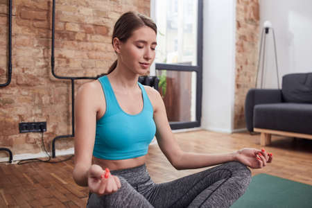 Adorable calm lady having meditation time in home interior