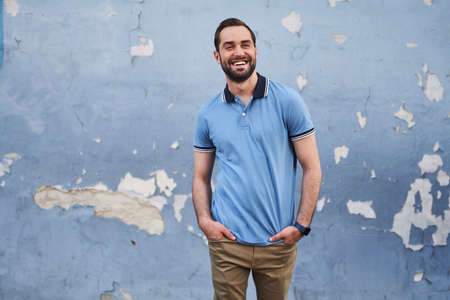 Happy young casual man on blue wall background