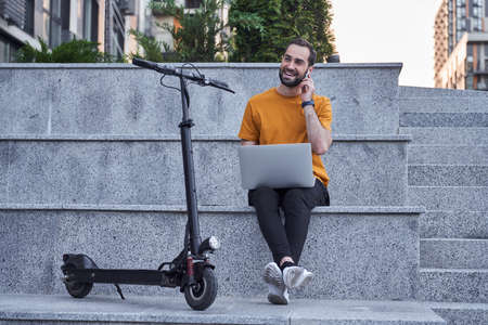 Happy man with gadgets and scooter in open air