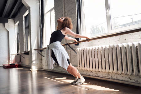 Female contemporary dancer stretching before class in studio