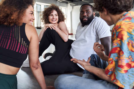 Four friends sitting on the floor in dance studio
