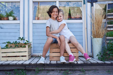 Cute little girl and boy hugging outside the house