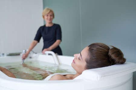 Young woman enjoying hydromassage in whirlpool bath