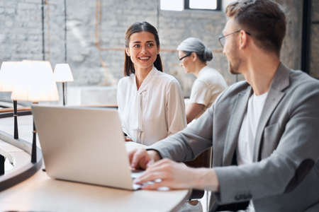 Cheerful female looking at the handsome man while sitting at the workplace