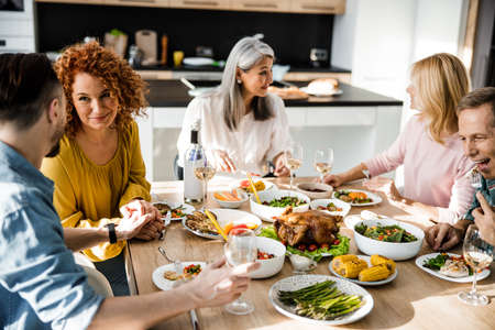 Friends talking at the festive table in a cozy home Banco de Imagens