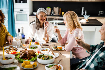 Smiling two women looking each other at the festive table in a cozy home