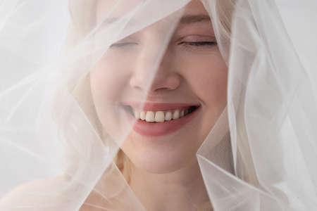 Cheerful young woman wearing beautiful white veil
