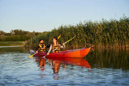 Happy family paddling kayak at sunset