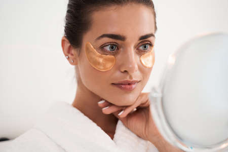 Woman applying gold eye patches Imagens