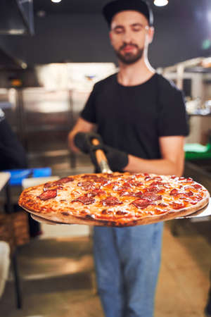 Pizzaiolo holding pizza on peel