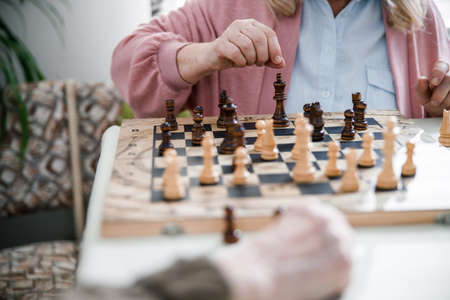 Retired couple playing chess on wooden table