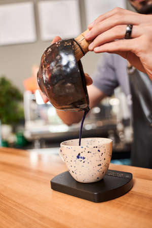 Man pouring blue matcha