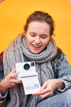 Girl takes photo out of the instant camera