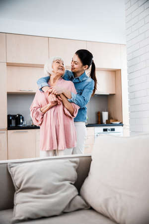 Happy grandmother and adult granddaughter hugging at home