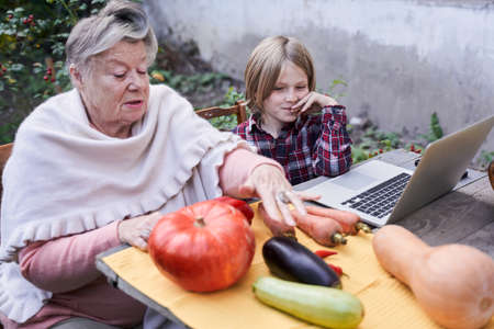 Grandmother telling to her grandson about the stages of cutting vegetables Stockfoto