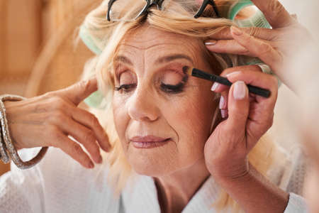 Mature female friends putting makeup