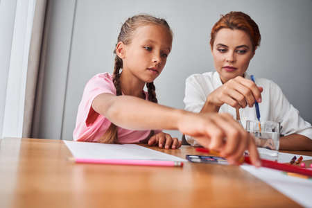 Girl drawing picture together with her mother