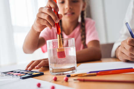 Girl dipping a paintbrush in water