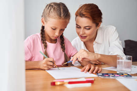 Mother drawing together with her kid