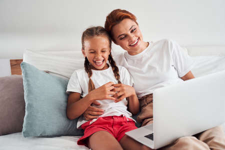 Mom and girl using laptop